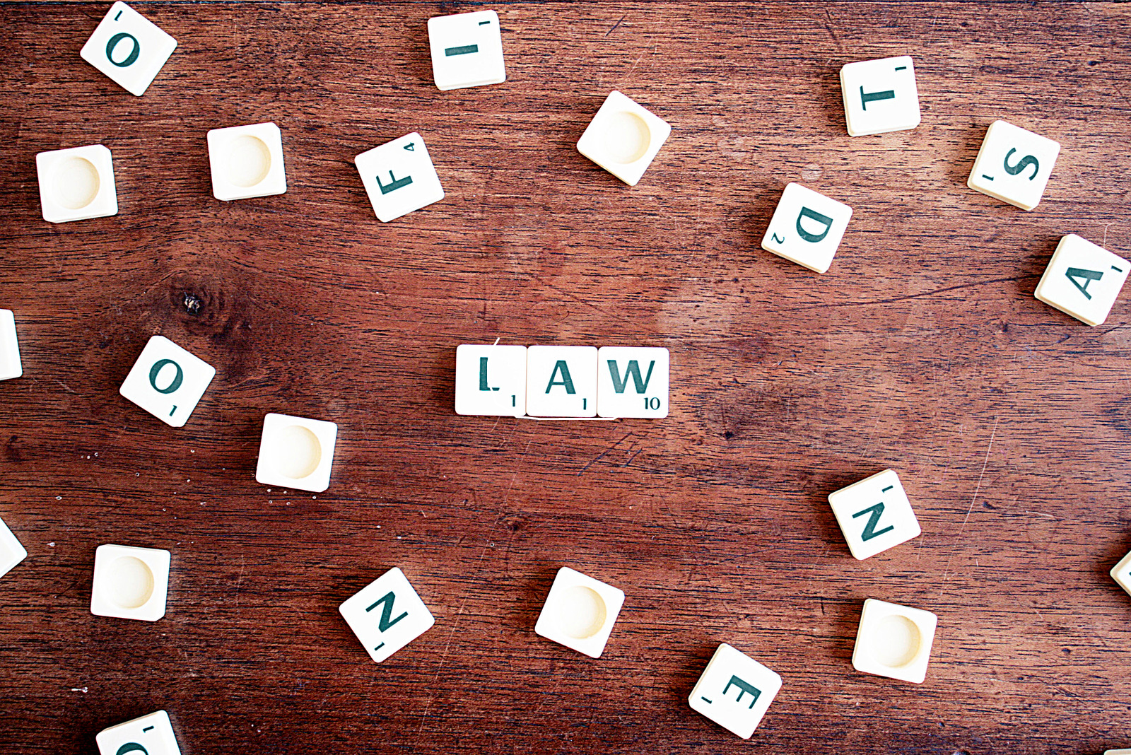 """Scrabble tiles on a table with three tiles in the middle that spell out """"law"""""""