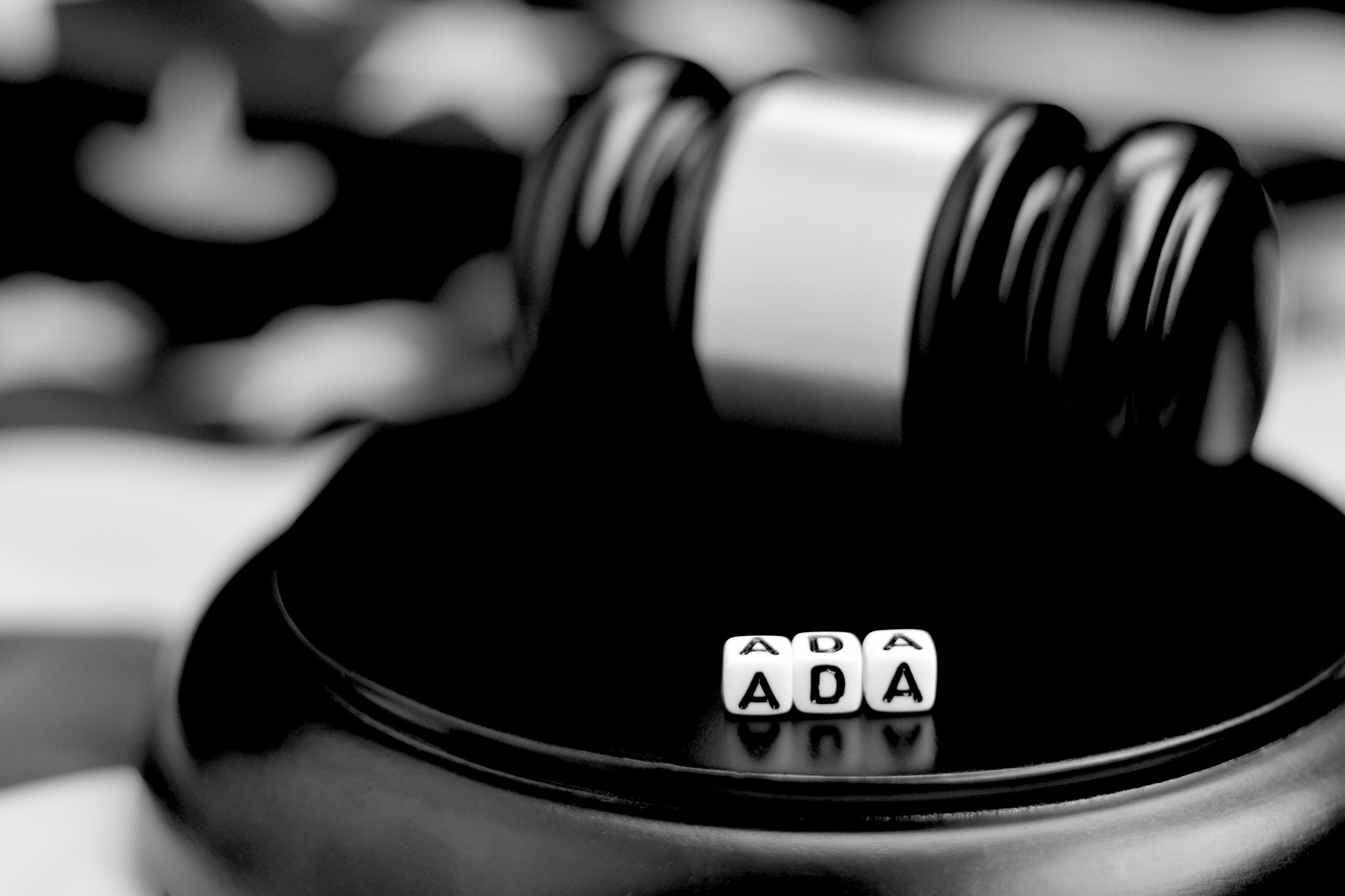 A judge's mallet with the letters ADA spelled out in dice in front of it