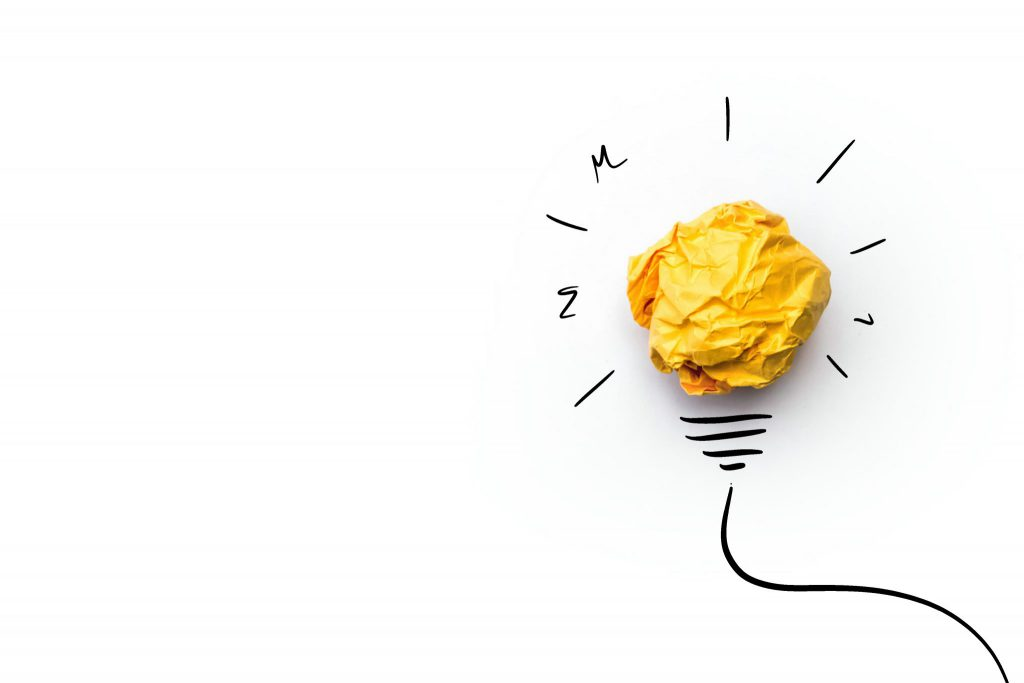 Lightbulb made of crumpled paper and idea marks