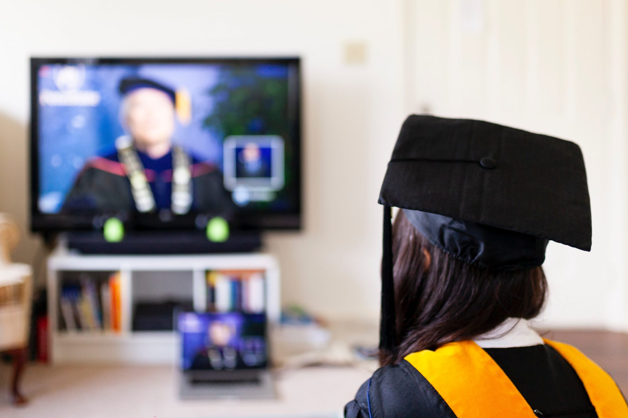 girl in cap and gown sits for virtual graduation